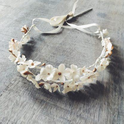Madrilene is een prachtige kroon met een dubbele rij van handgemaakte bloemen van koud porselein met een vleugje goud. Het wordt geleverd met een afneembaar lint.